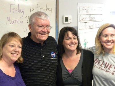 Teachers embrace their guest of honor (L-R): Jill Lipski, Fred Haise, Robbin VonDerBruegge & Mrs. Fruge.