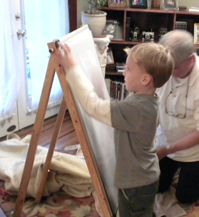 Charlie finally gets past the protective wrapping to his birthday present..an easel on which to make art.