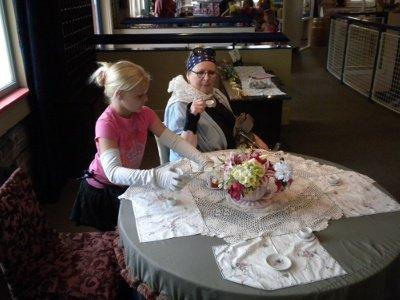 Granny enjoys High Tea and a scone served by gloved servant Sara Riley.